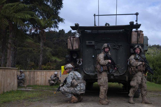 U.S. Army soldiers, 25th Infantry Division, and New Zealand Defence Force soldiers, 1st New Zealand Brigade, prepare to move while taking cover behind a light armored vehicle during Exercise Kiwi Koru Nov. 13, 2014, outside of Whangamomona, New Zealand. Exercise Kiwi Koru training elements included combat lifesaver training, Law of Armed Conflict scenarios, counter improvised explosive device training and a force-on-force tactical exercise. Approximately 60 Soldiers from the 25th Infantry…