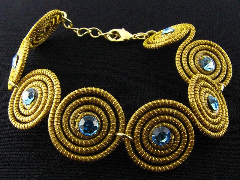 Pulseira de capim dourado com espirais médias e zircônia na cor azul-clara