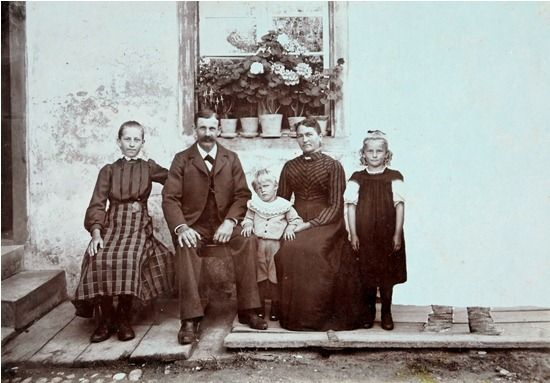 1900: Wegretuschiert RETUSCHIERTE GRUPPENAUFNAHME einer fünfköpfigen Familie vor einem Geranienfenster. o.J. [um 1900].