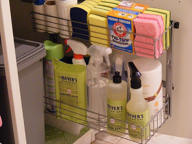under kitchen sink organized cleaning products and recycle/trash bins