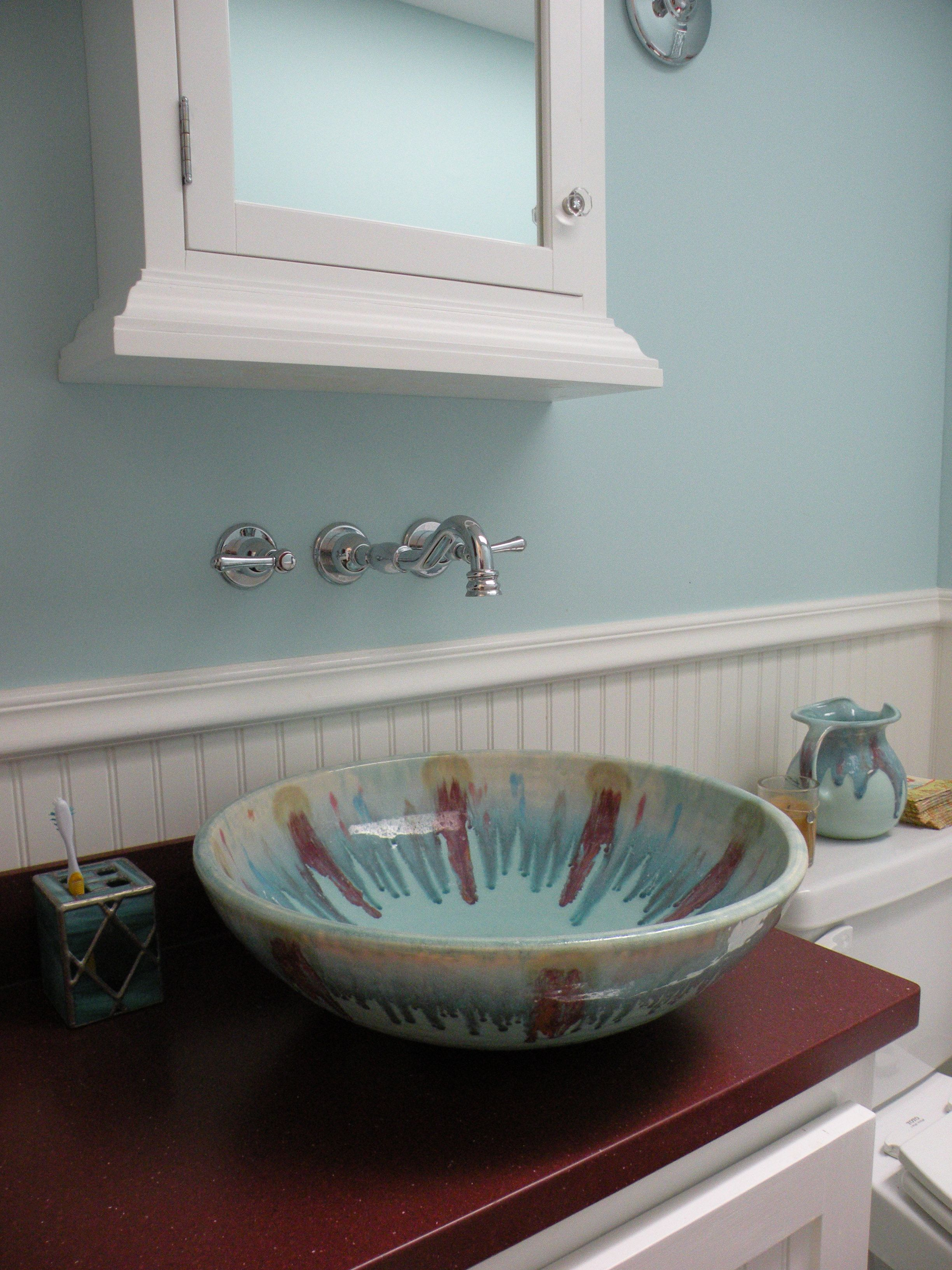 Handmade ceramic bowl was used for a sink.  Note the pitcher in the background.  They were both made by Dan Lasser  http://lasserceramics.com/  When you use a bowl for a sink, it's best to do a wallmount faucet.  The challenge is that then your mirror/medicine cabinet has to be hung higher so make sure you can still see yourself.  The countertop is corian in the red to pick up the red in the bowl.