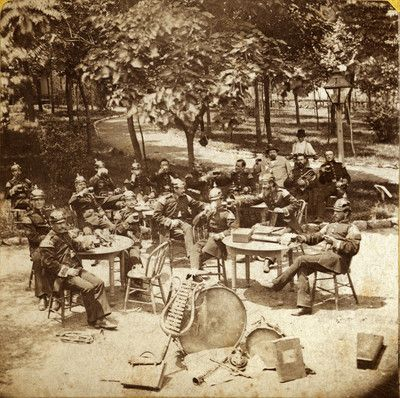 Band members seated at tables at Schnaider's Garden. Chouteau Avenue between Mississippi and Armstrong. (1870)