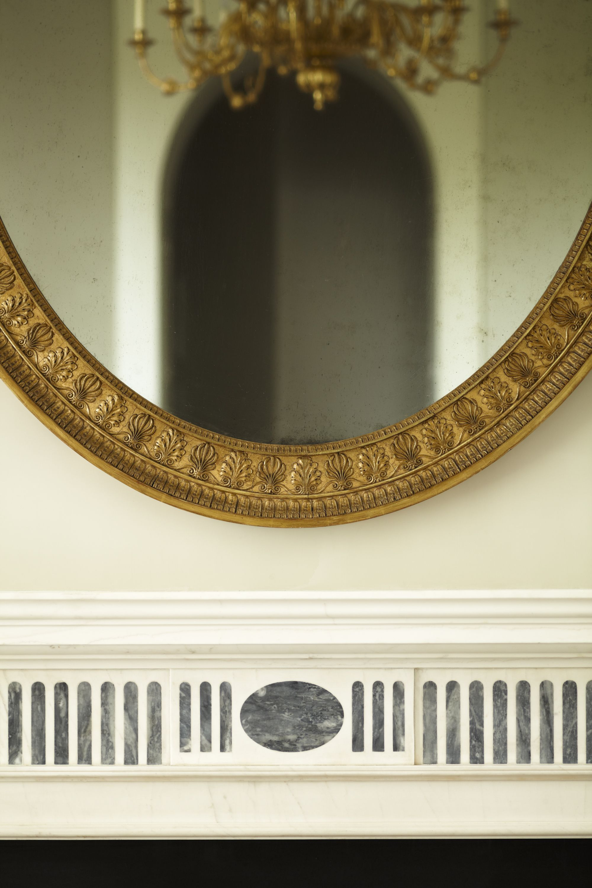 An oval mirror repeats the geometry of the inlaid marble mantel and the arched doorway