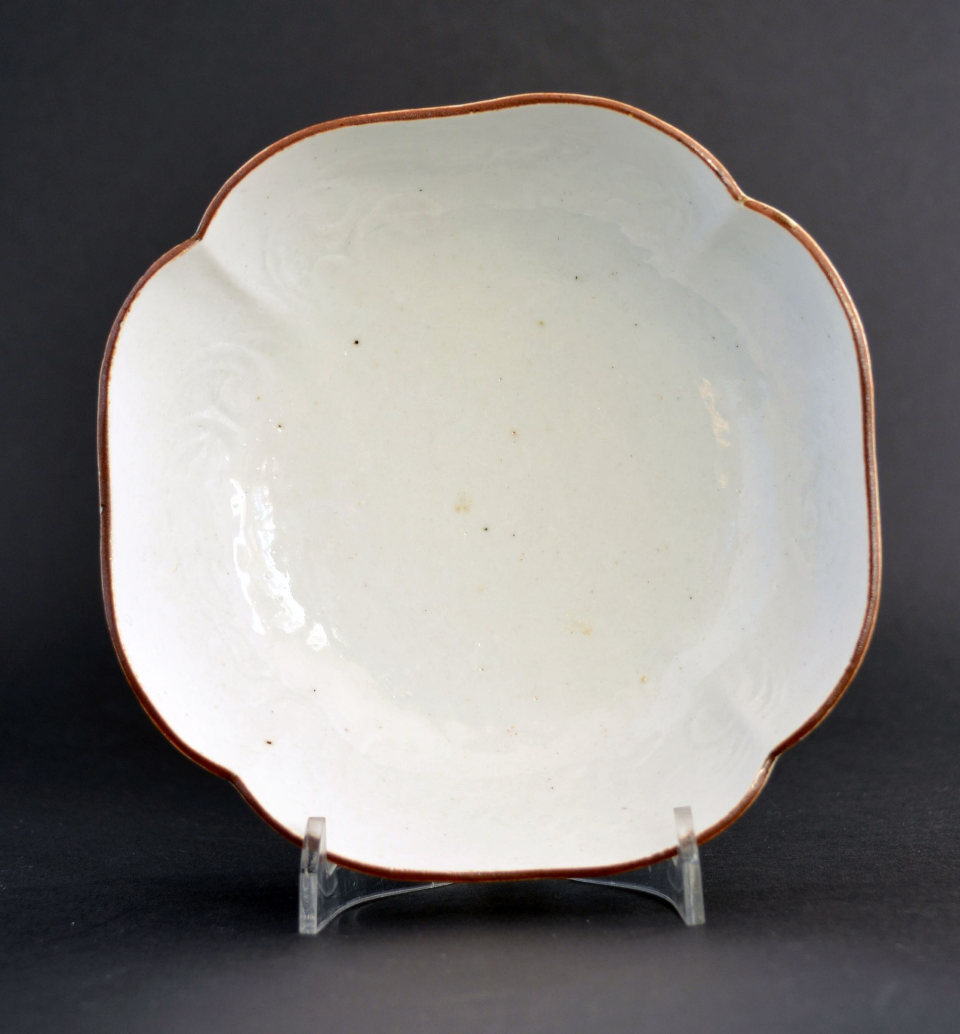 A 17th Century Kakiemon Nigoshide Porcelain Bowl c.1670-1700. The Square Lobed Form with Steep Sides is Lightly and Indistinctly Moulded with What Might be Flowers. The Rim is Dressed with a Brown Iron Rich Kuchibeni (Meaning lipstick).