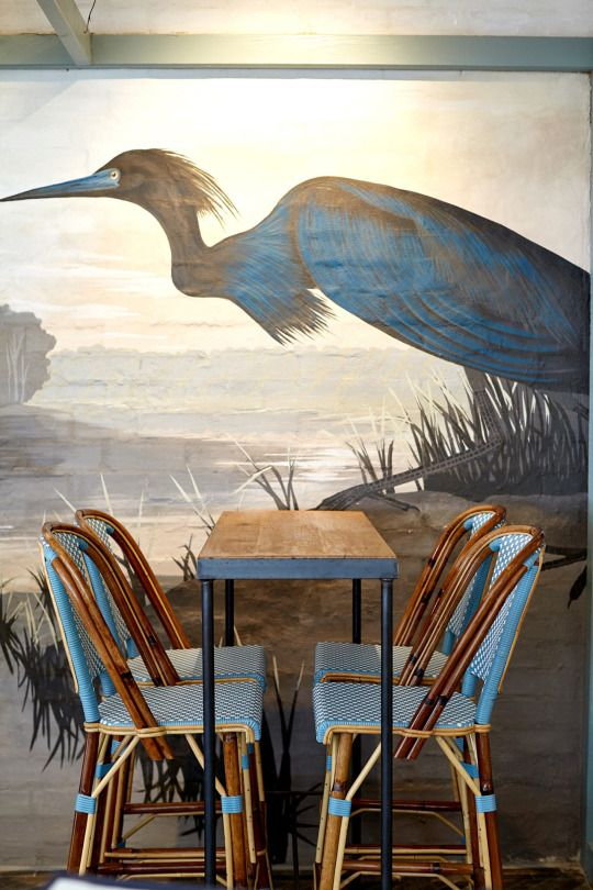 Vogue Living, painted wall mural as art, woven blue dining chairs, bird wallpaper