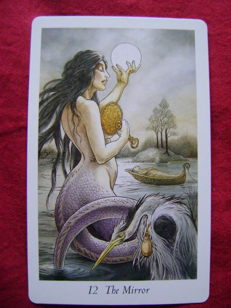 Wildwood Tarot - The Mirror (MA 12) - The Lady of the Lake, with a serpentine lower body, and flowing dark hair, holds the full moon in one hand and a mirror in the other. A heron is in the foreground. In the distance, a boat carries a corpse to a tiny island