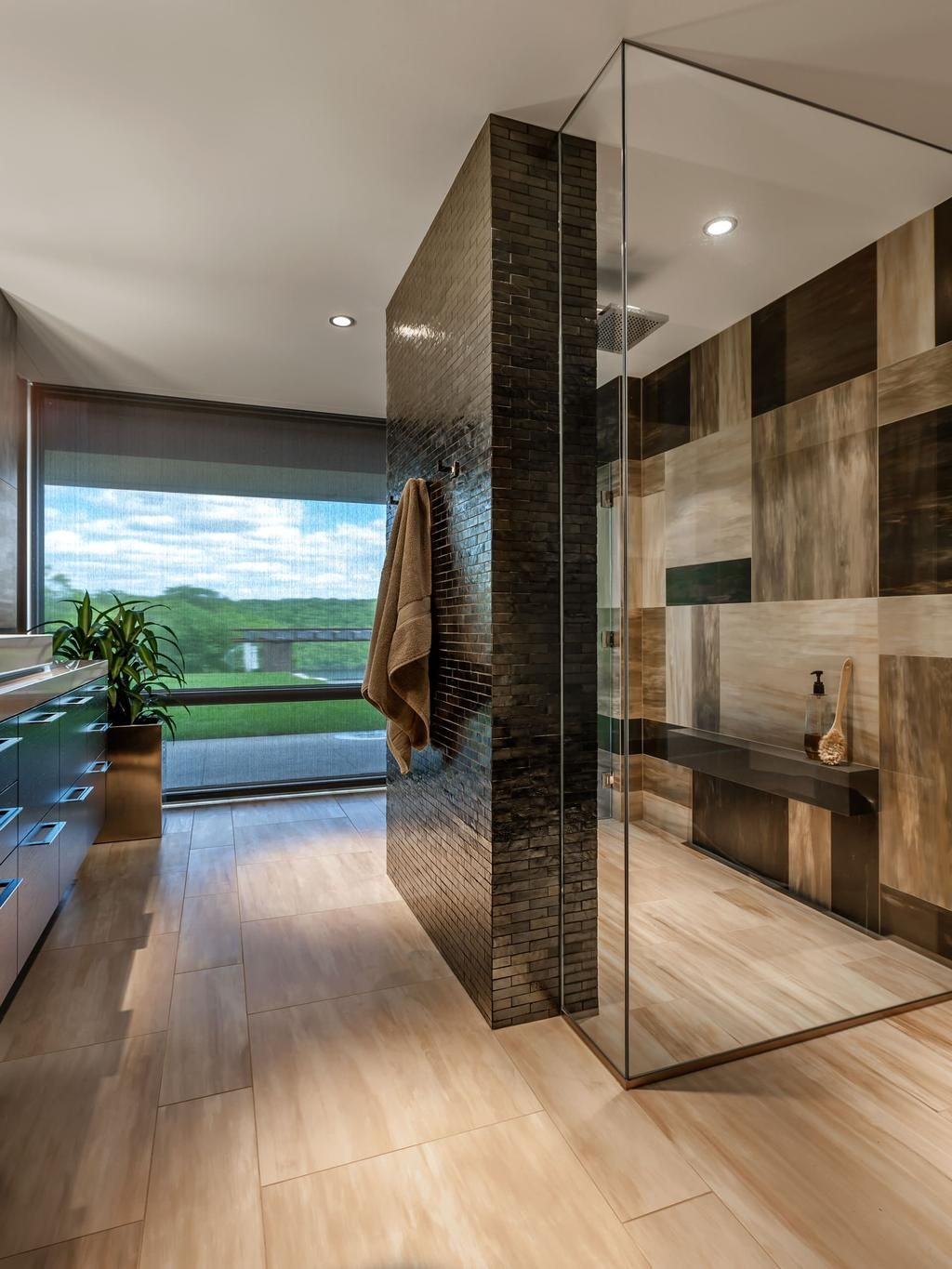 Stunning Bathroom With A Large Walk In Shower Surrounded By Black Glass  Tile.