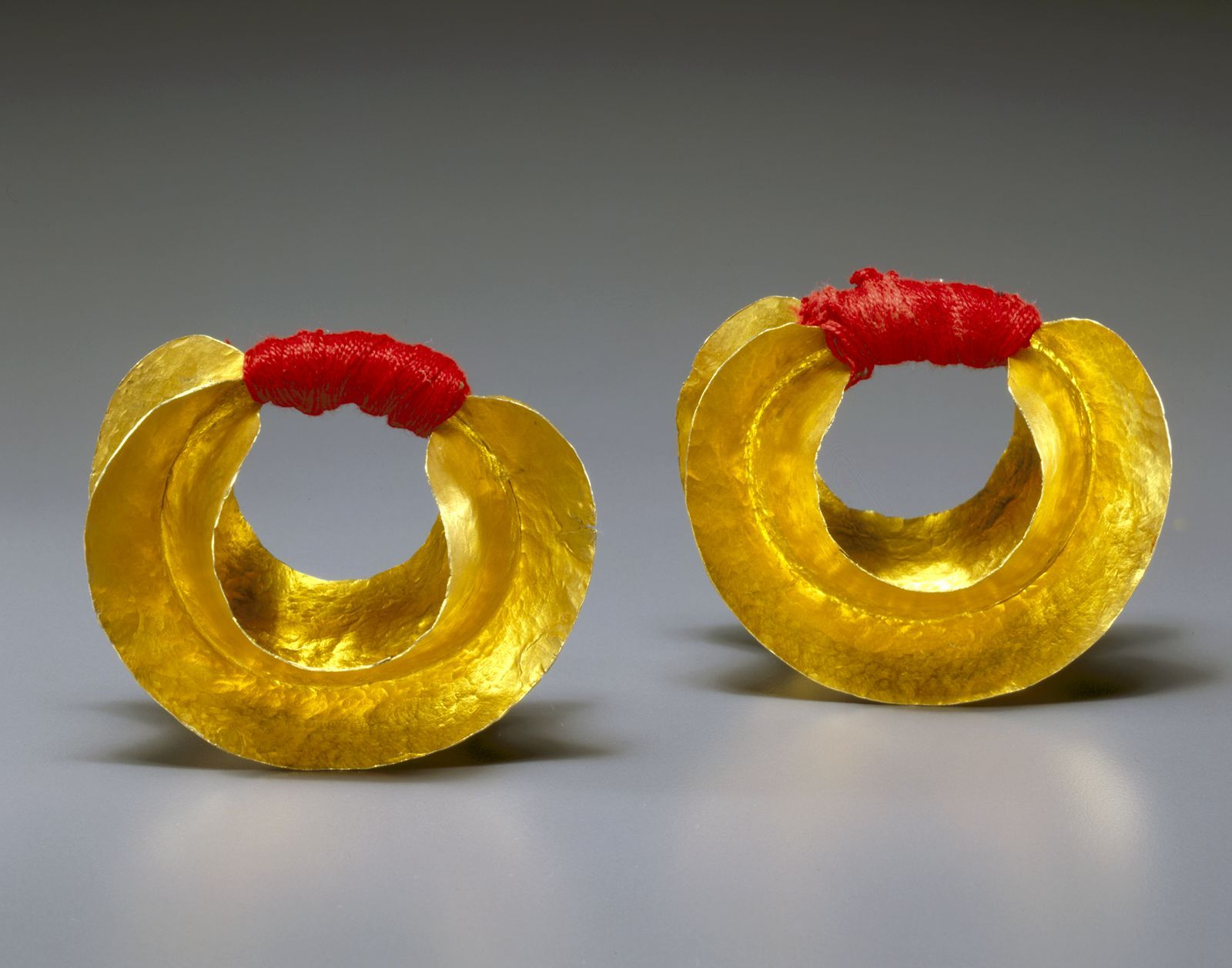 Africa | Fulani earrings.  Gold and fiber.  Mid 20th century | Jewelry items such this example form an important part of a woman's personal prestige and wealth.