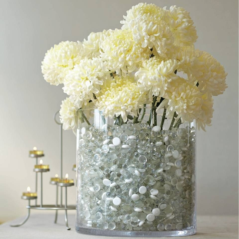 White flowers in majestic glass vase clear river rocks