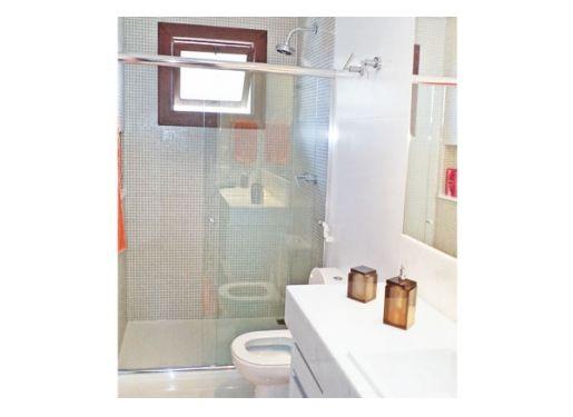 O banheiro de 3 m² segue um padrão mais clean. Para brincar um pouco com o espaço, a arquiteta investiu em pastilhas 2 x 2 cm. Elas revestem apenas a área do box para que, além do belo contraste, também haja economia no custo do banheiro.