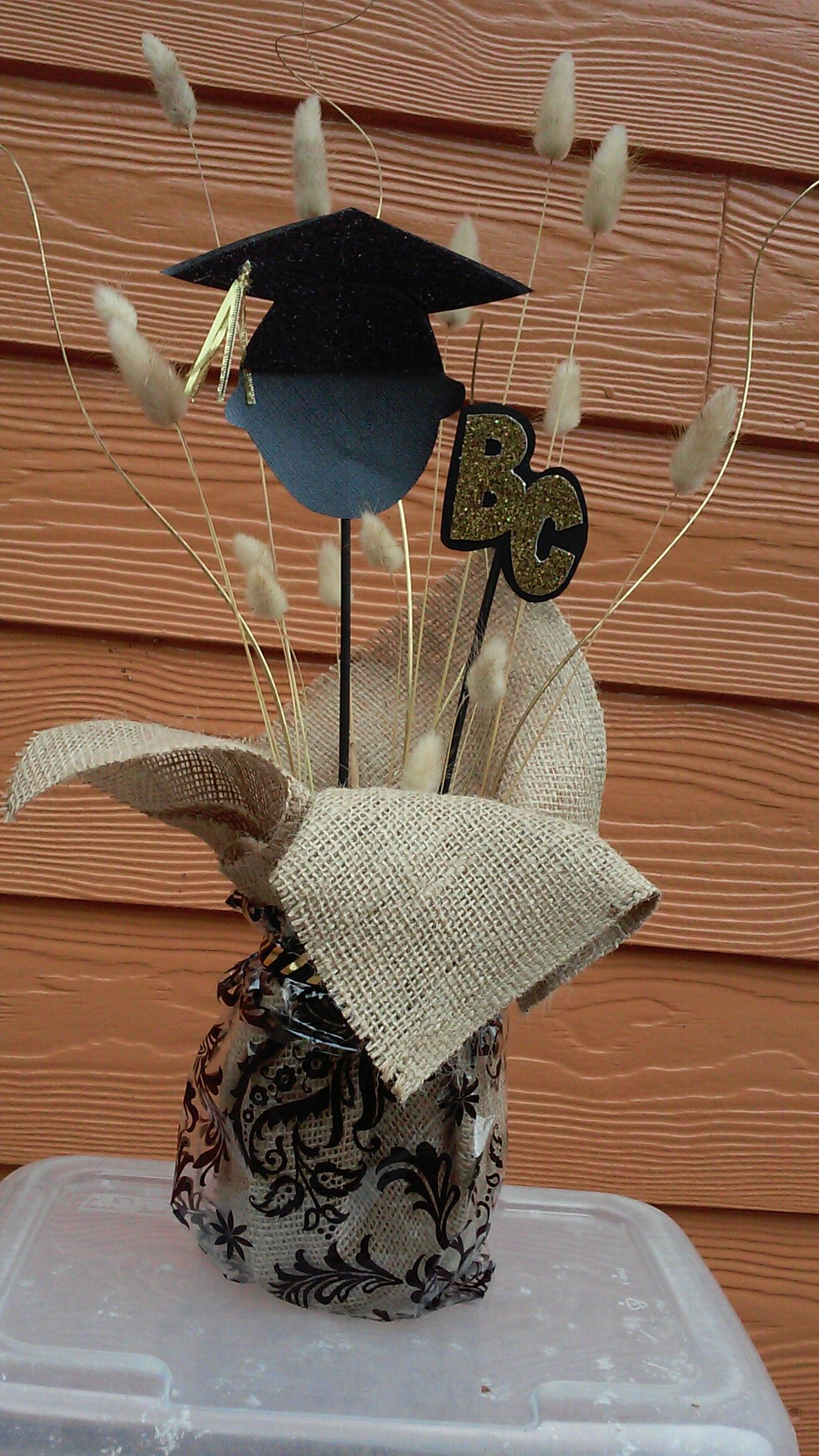 Graduation Center Piece. Mason jar filled with sand,  burlap, cellophane gift bag, ribbon, and added decorations.