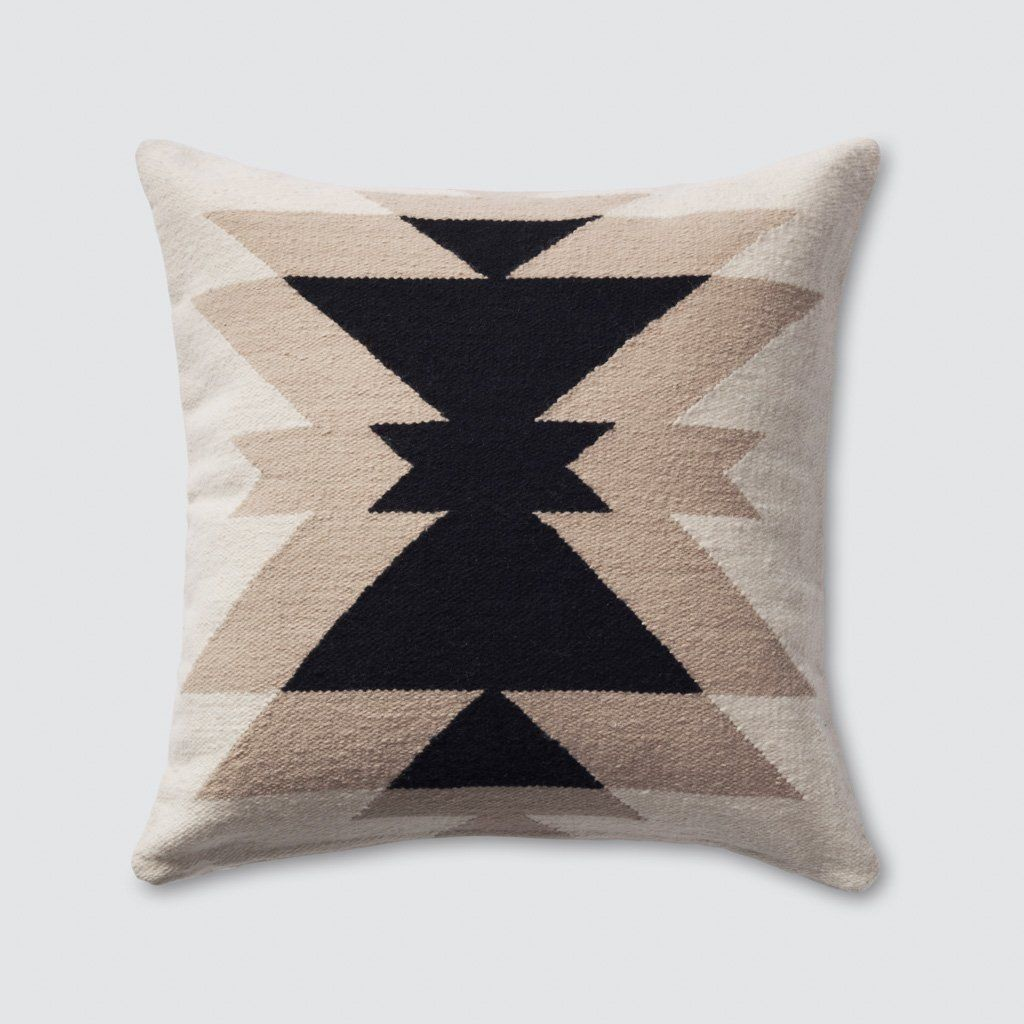 A neutral accent pillow that's far from boring. A mix of soft almond and tan hues, accented by bold black, this handsome fellow packs a big design punch. Throw it on a couch or style it on a bed - its graphic, geometric pattern brings a modern feel to any space.Handcrafted in a small workshop in Lima, Peru, this piece takes one day to complete. All made start-to-finish in a fair trade environment.This pillow comes ready to style. Cruelty-free down alternative insert included.