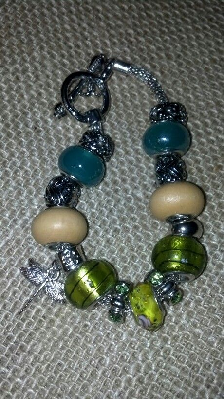 Dragonfly charm. Wooden,  mixed green colored glass, crystal and silver beads on a silver slide bracelet.