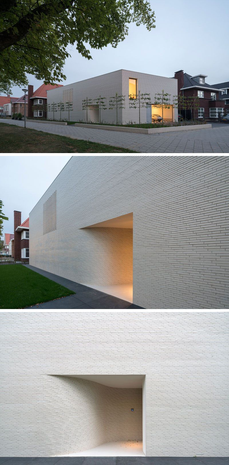 The exterior of this modern house is made up of white bricks with minimal windows. The entrance to the home is tucked away within a small alcove.
