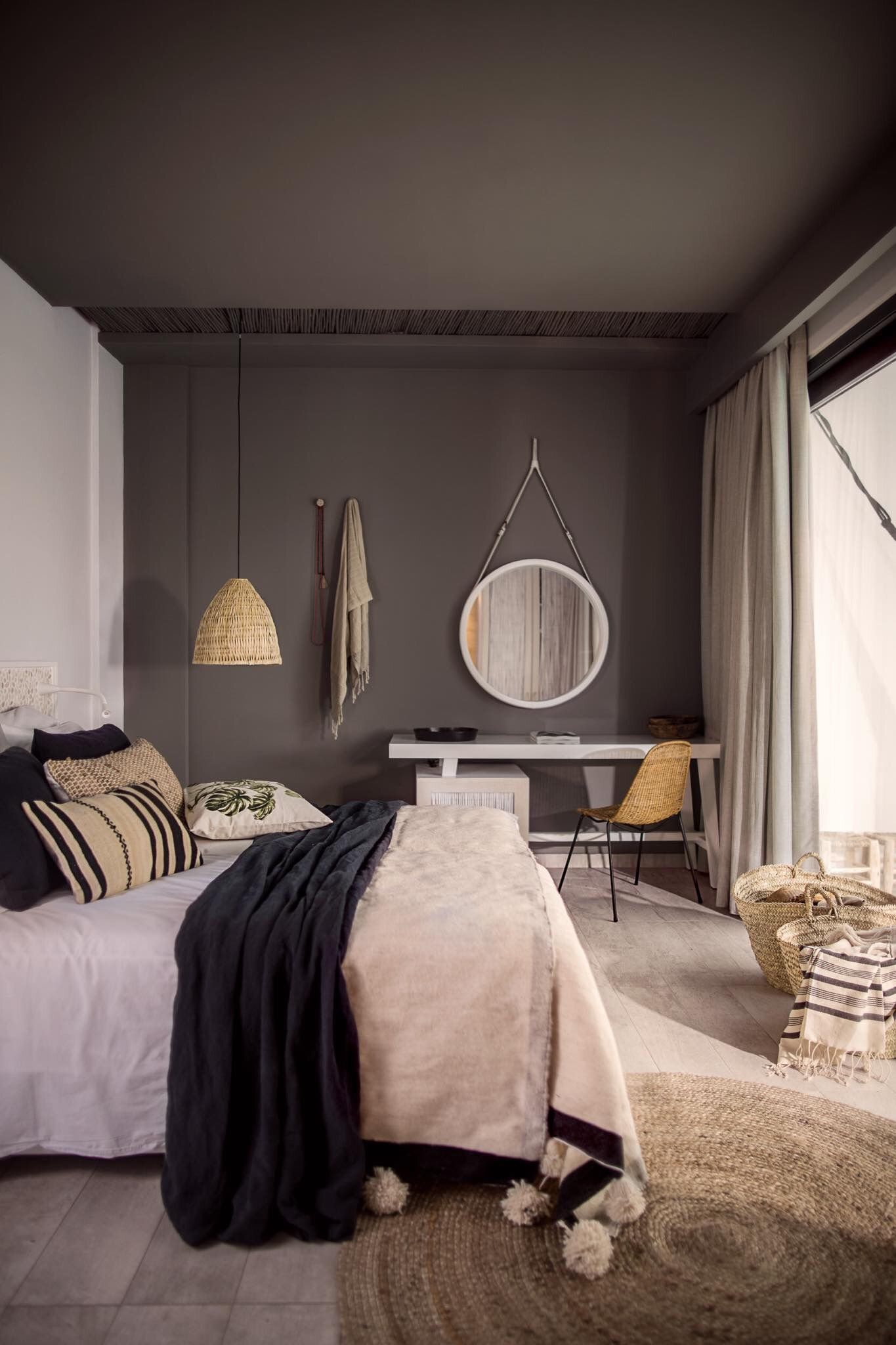 This is a great way to make grey feel really warm in a bedroom space Love the jute rug and moroccan pom pom blanket