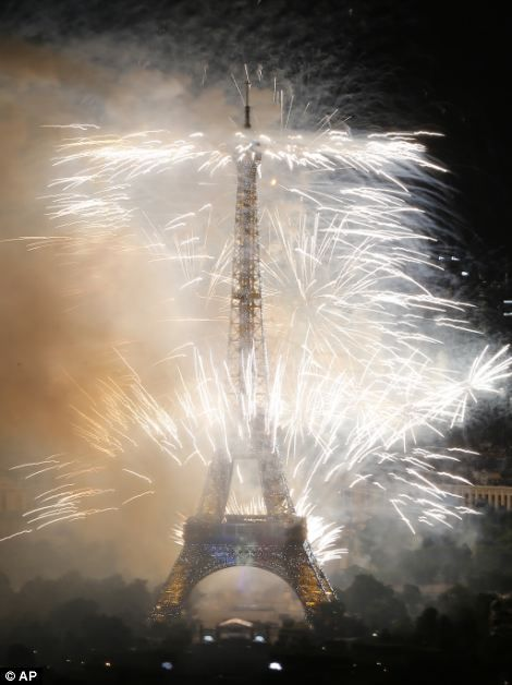 Bastille Day fireworks explode over the Seine River next to and out of the Eiffel Tower in Paris