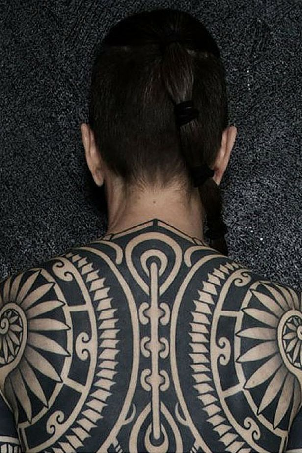 Woman covered from head to toe in huge intricate tribal tattoo