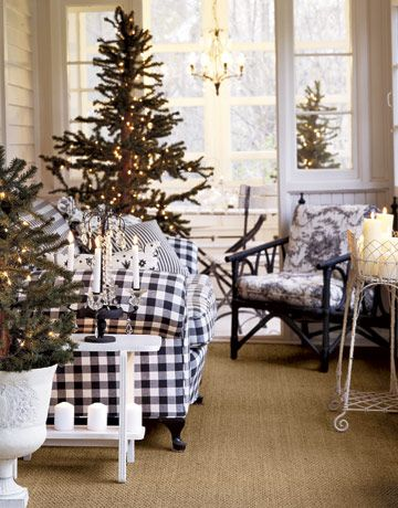 Enclosed Winter Porch  -- Synthetic trees on an enclosed porch, decked only with white lights, cast their welcome to the wintry street.