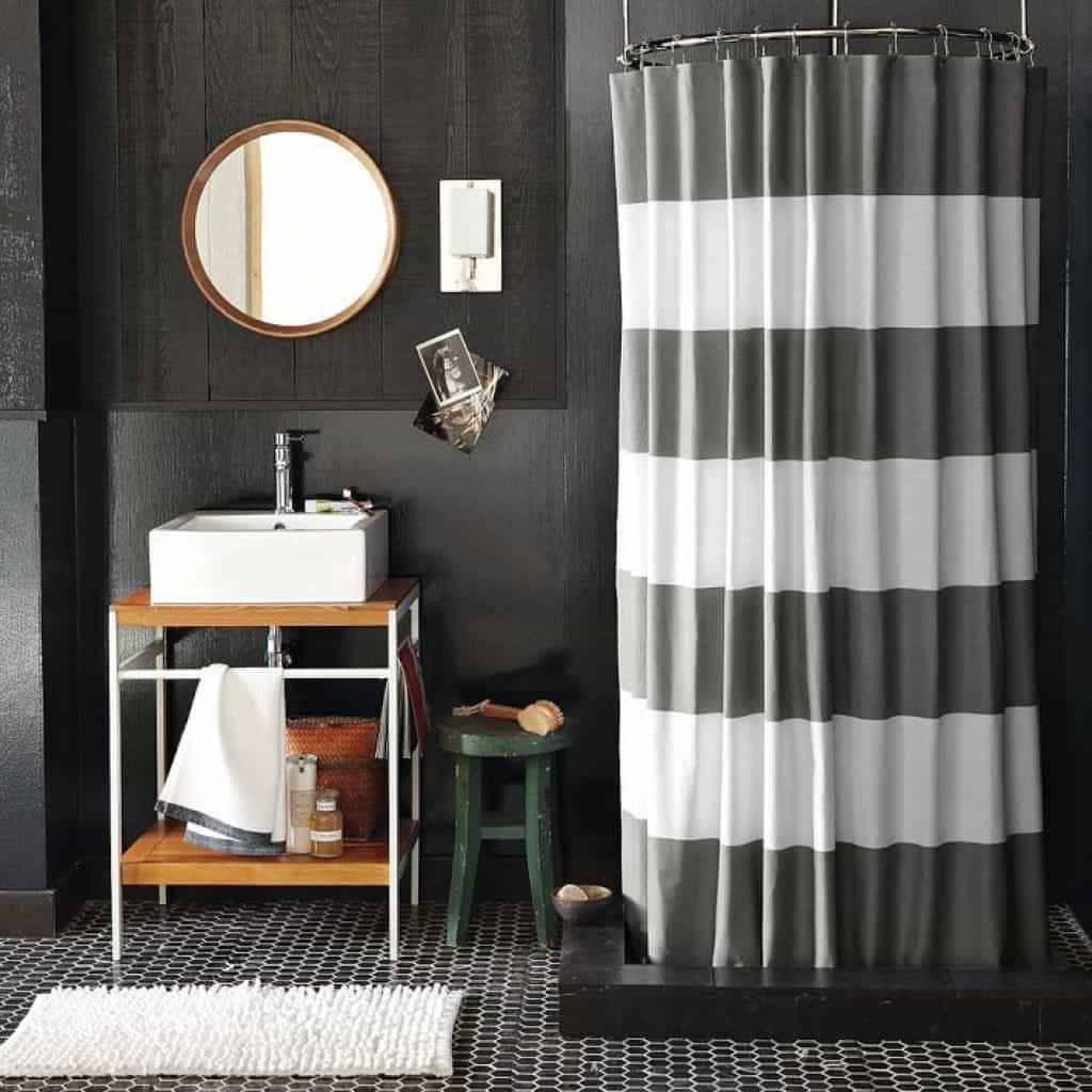 Masculine bathroom with stripes shower curtains and black walls also