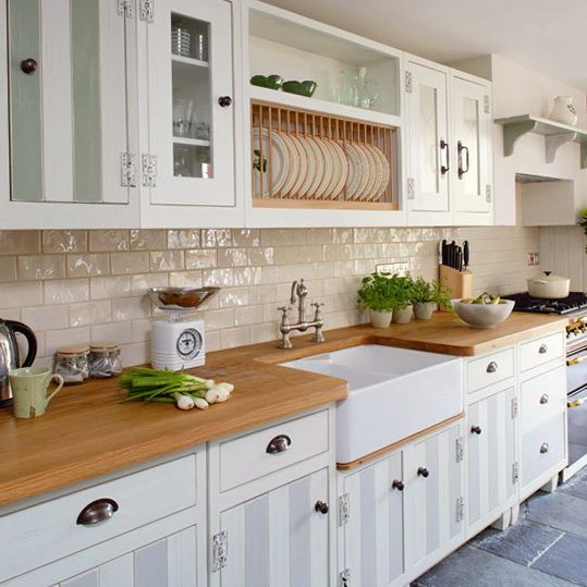 classic kitchen top is natural wood patterned with white subway tiles for backsplash