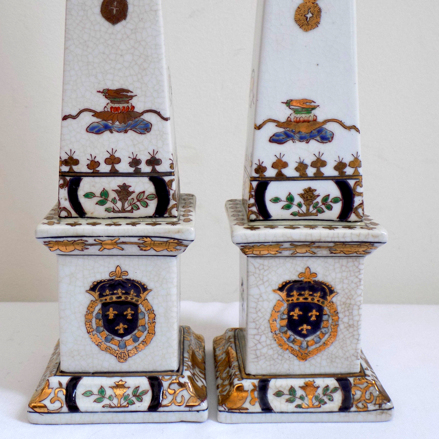 """Nice Pair of Spanish Hand Decorated Gilded Porcelain Obelisks - The underside of both is signed in red as follows : """"Christine Cano Pintado a Mano by Nelson""""; one bears the number 124. - Detail of Coat of Arms."""