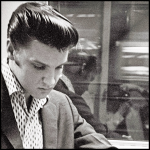 Alfred Wertheimer is seen in the reflection of the glass while taking a photo of Elvis on a Memphis-bound train. 1956 | Remembering Al Wertheimer Posted by Elvis Presley's Graceland on Oct 23, 2014 |*