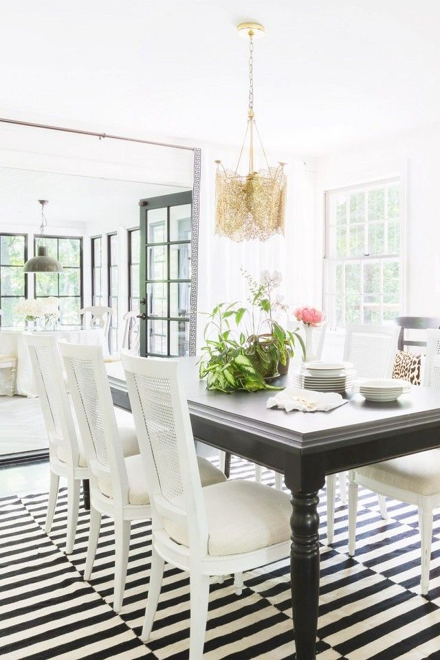 Formal Dining Room With A Low Hanging Gold Chandelier Simple Black Table And White Chairs