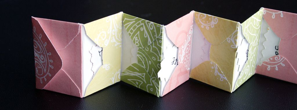 Followed this tutorial: www.paper-source.com/cgi-bin/paper/howto/ideas/envaccordi...  and used mini-envelopes formed from a paper punch that cuts and scores ready-to-fold shapes.  Each pocket contains a line from a short poem.