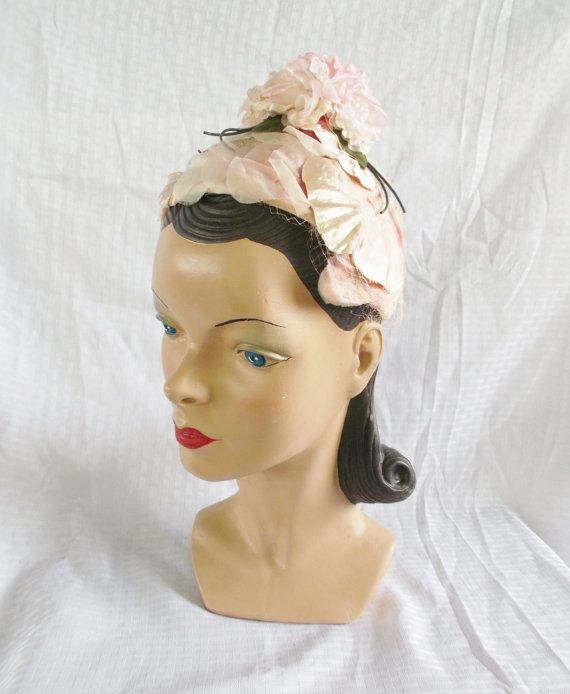 Darling pixie hat from the 50's. It consists of a hardened mesh base and is covered with pink petals. On top is a cluster of pink roses. So cute! Label: none.
