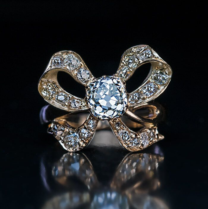 circa 1890 An antique 14K gold ring is designed as a bow embellished with diamonds. The center stone is a sparkling old cushion cut diamond measuring 6.5 x