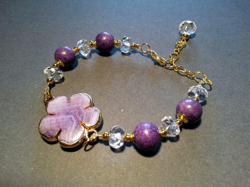 Bracciale con pietre ricomposte, cristallo di rocca e fiore in agata viola, montati con componenti e catena in metallo color oro. Realizzazione artigianale.