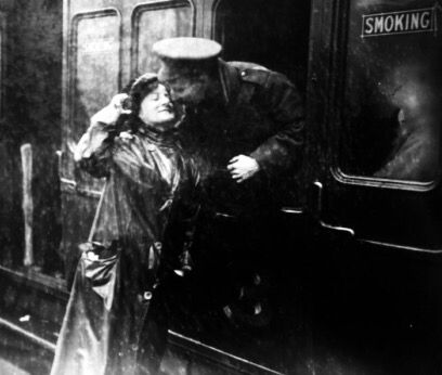A soldier saying goodbye to a loved one in the rain at Victoria station, London, as he leaves for the western front during World War One