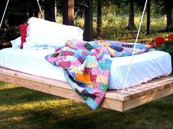 Bed van pallets met matras in de tuin, hangend aan een boomtak ...