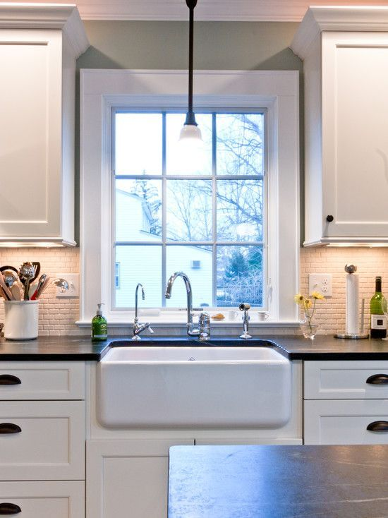 Photo of soapstone counter, farmer sink, white cabinets with detail on bottom, mixed meta…