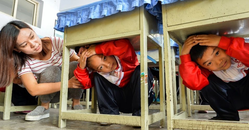 20160512 - Estudantes se protegem embaixo das carteiras durante treinamento para ação em caso de terremoto na cidade de Xingtai, no norte da China. O governo do país instituiu 12 de maio como o Dia da Prevenção de Desastres e Redução de Danos Imagem: Mou Yu/Xinhua