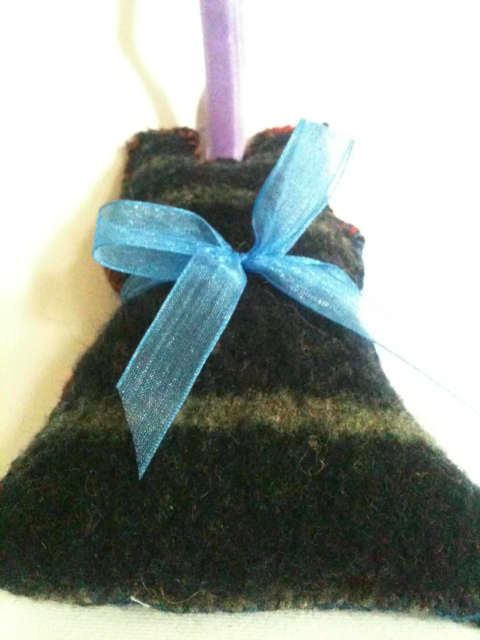 Hanging, felted dress decoration, made from a wool jumper, shrunk in the washing machine. She has an organza ribbon bow & velvet ribbon hanging tag.