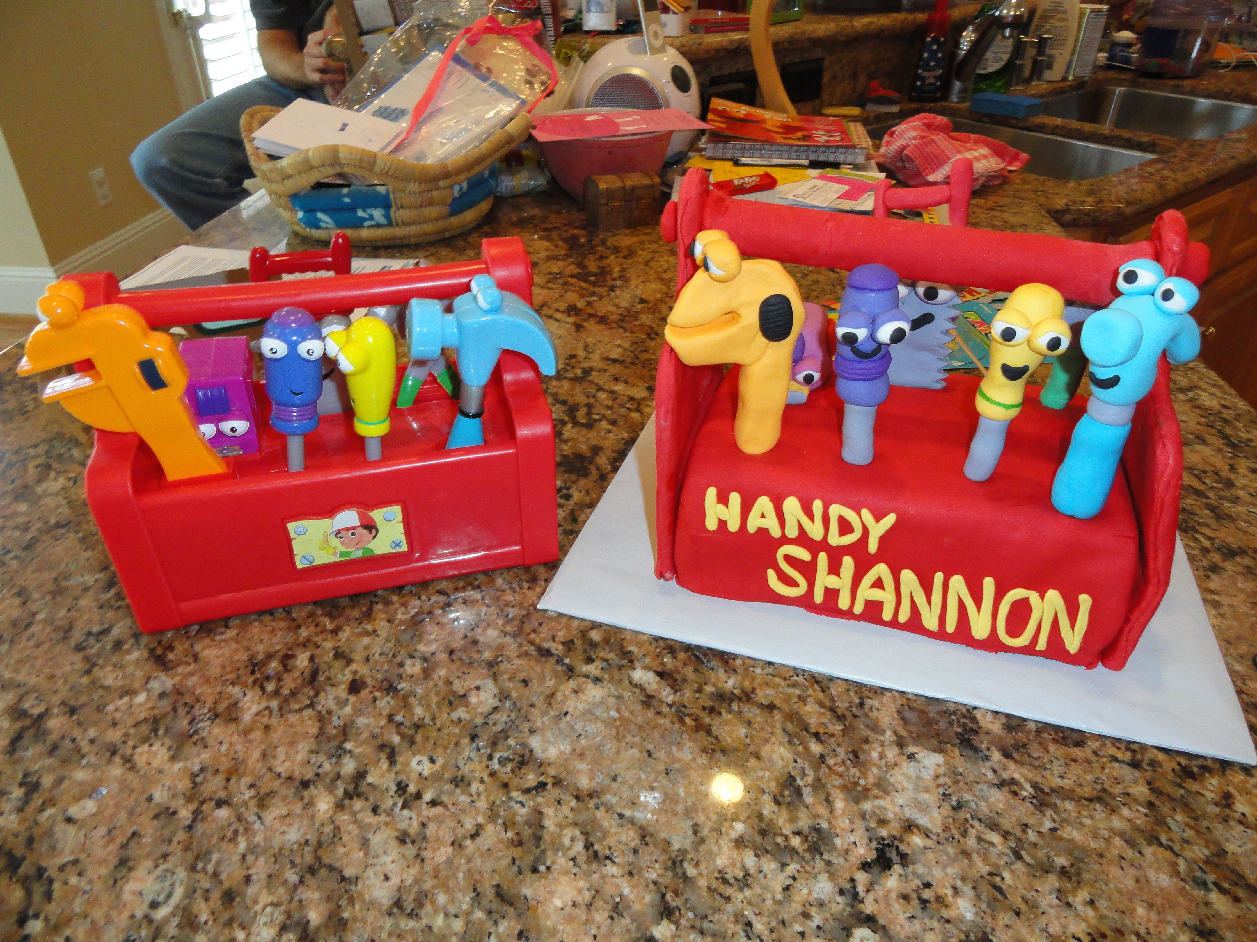Handy Shannon :)  All the tools are gum paste, the tool box is a loaf pan, ends are fondant, handle is a plastic dowel wrapped in fondant.