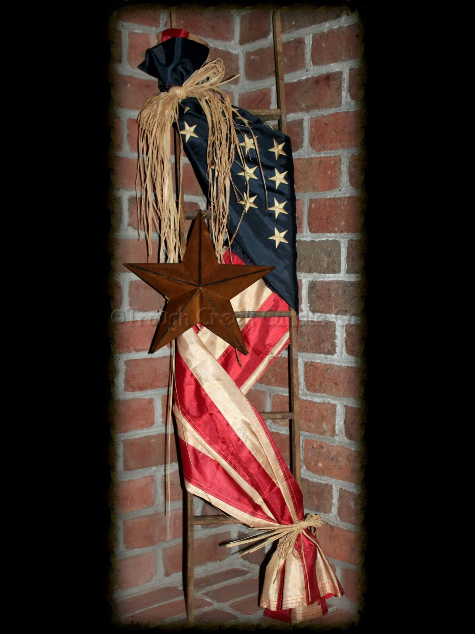 "Adorned with a tea-stained *replica* Americana flag and accented with a rusty star, this ladder will be a great addition to any Americana home decor or any front porch. This American Flag ladder measures approx. 48"" high."