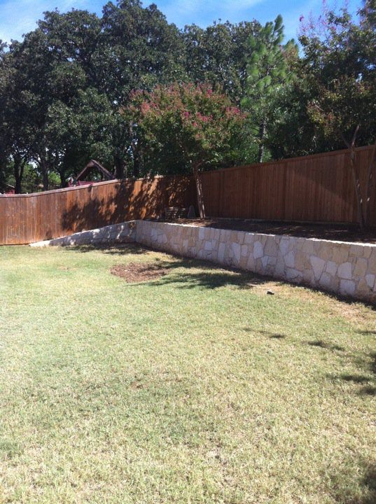 change the wooden fence to white and a stone retaining wall for the ...