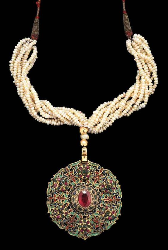 Morocco | A gemset (central red garnet set in a band of small emeralds) and enamelled gold circular pendant (Tazra), suspended on multiple seed-pearl stands.  The back of the pendant is similarly enamelled | Fez, late 18th century | 45,600£ ~ sold ( Apr. '07):