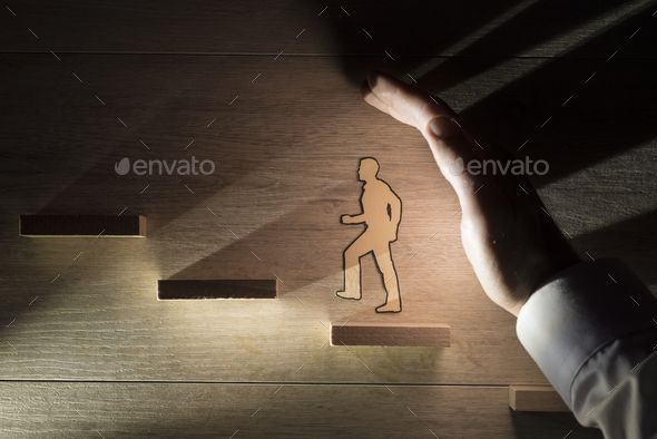 Hand protecting a paper man during progress by Gajus-Images. Conceptual close-up of the hand of a man protecting a paper man during progress while climbing stairs against wooden ... #AD #man, #progress, #Gajus, #Hand