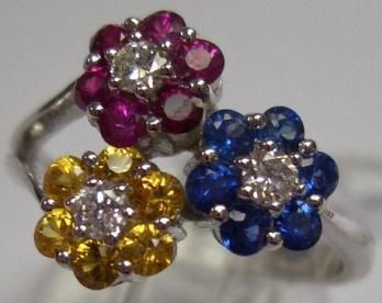 Triple flowers ring in grey gold (4g20) set with 6 round rubies 0.40ct (0.38ct), round sapphires 0.35 ct (0.36), 6 yellow round sapphires 0.35 ct (0.37) and 3 modern-cut white diamonds 0.20 ct (0.19). Ring size (FR): 54