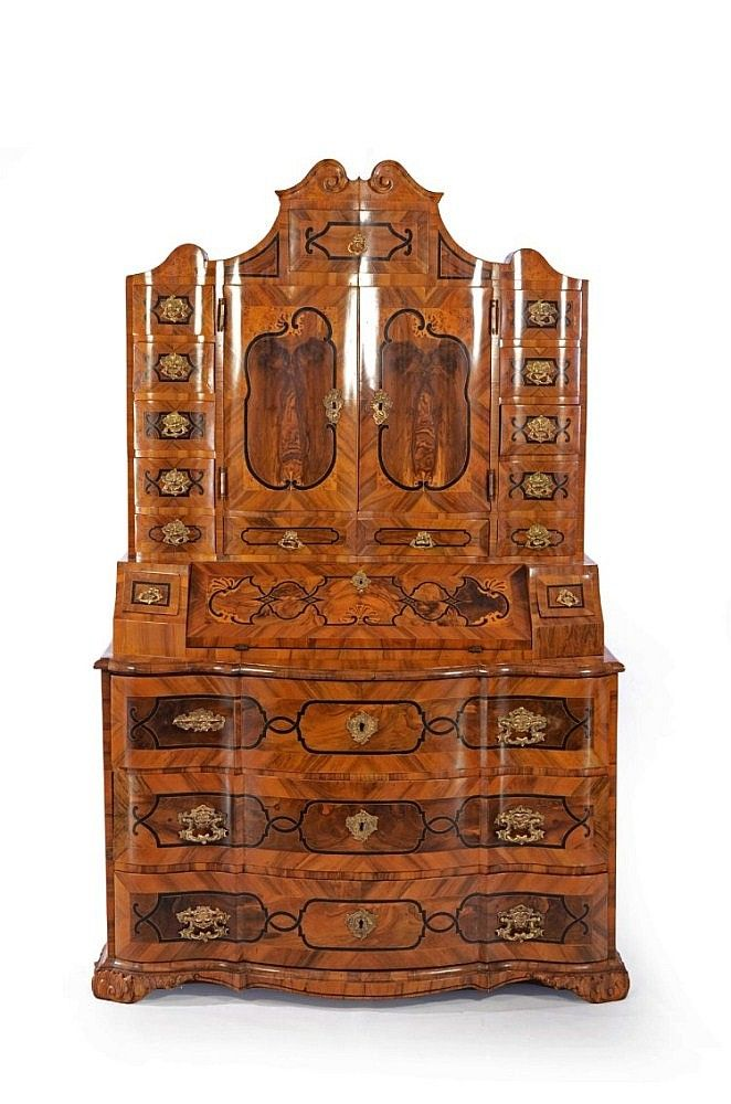 Bohemia, 1730s-1740s. Baroque inlaid secretaire with dynamically convexly-concave curve. Two-door upper part hides ten small-sized drawers which border a central part with one shelf and lockable tabernacle. On its both sides there are placed five drawers above each other and one smaller one on the upper part in volute top. Hinged writing board, bordered with a narrow drawer on both sides, covers a group of four others. The lower part is comprised of three big lockable drawers. 205x120x55 cm.
