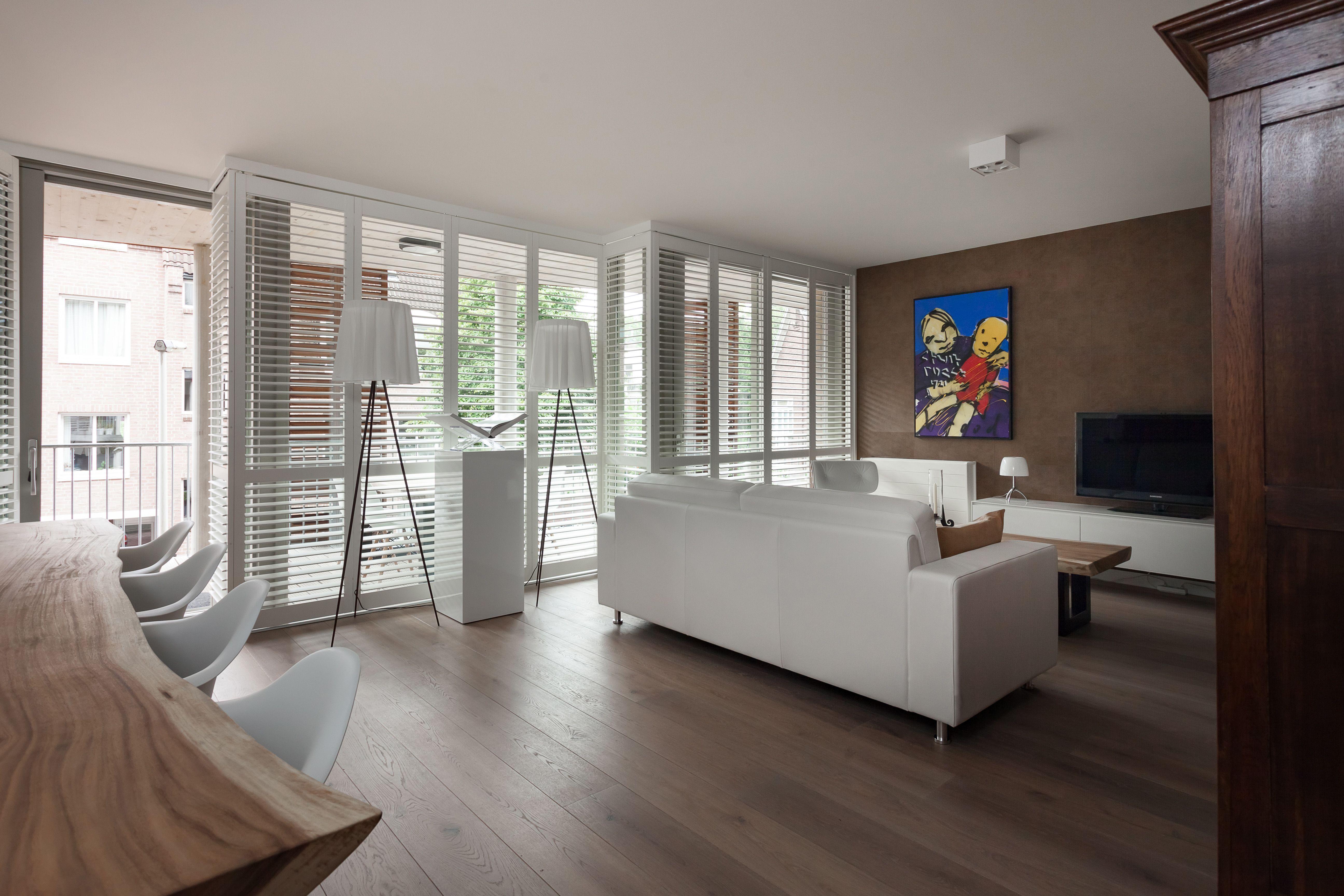 Witte moderne shutters in woonkamer. Gemonteerd in railsysteem en ...