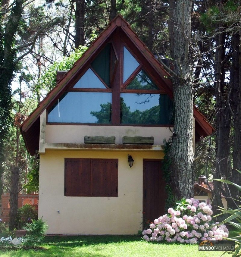 Fachada simple de dos pisos con detalles en madera en puertas y - fachada madera