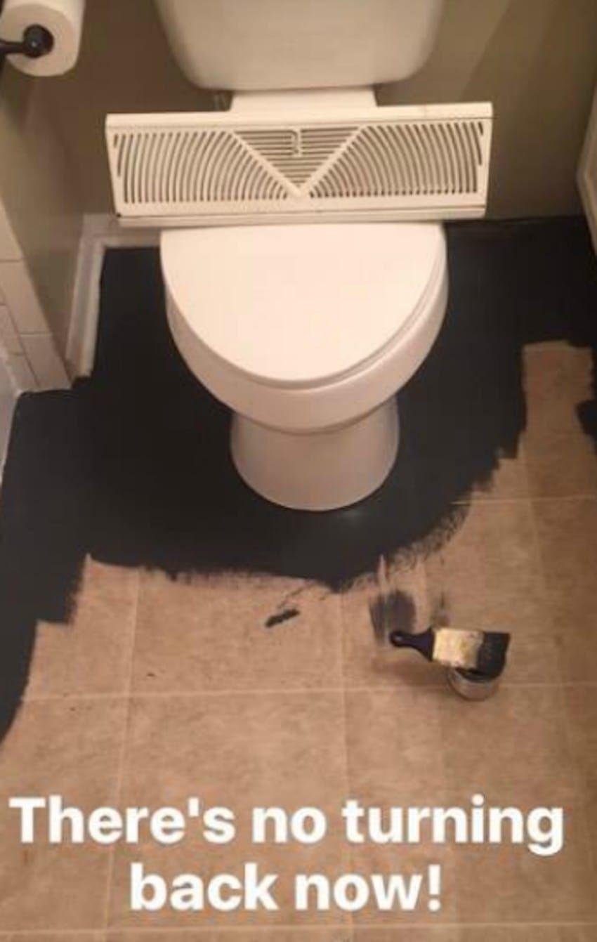 comienza a pintar el suelo del bao de negro para en algo