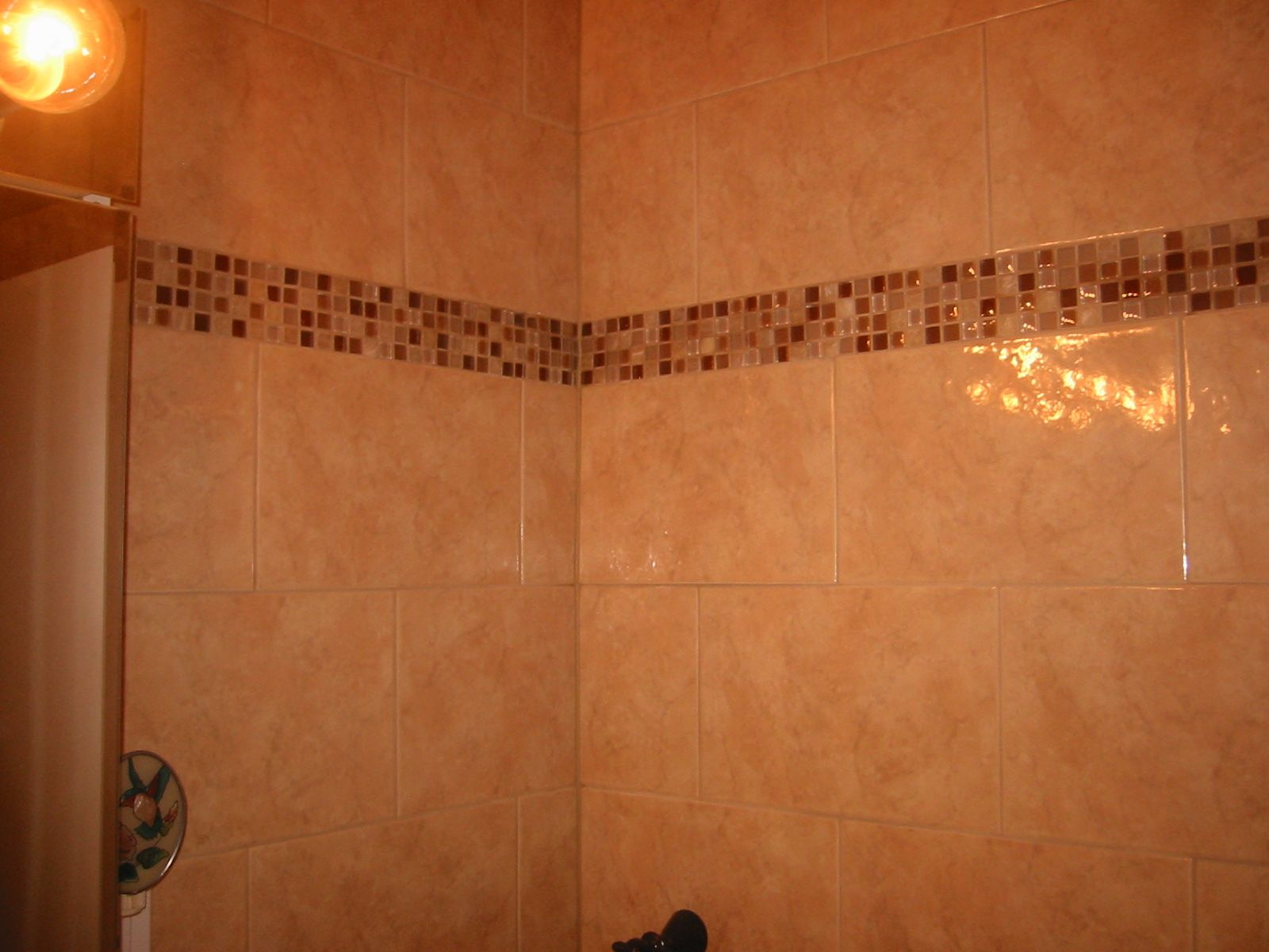 Corner ceramic tiled walls with color glass mosaic tiles as a trim ...