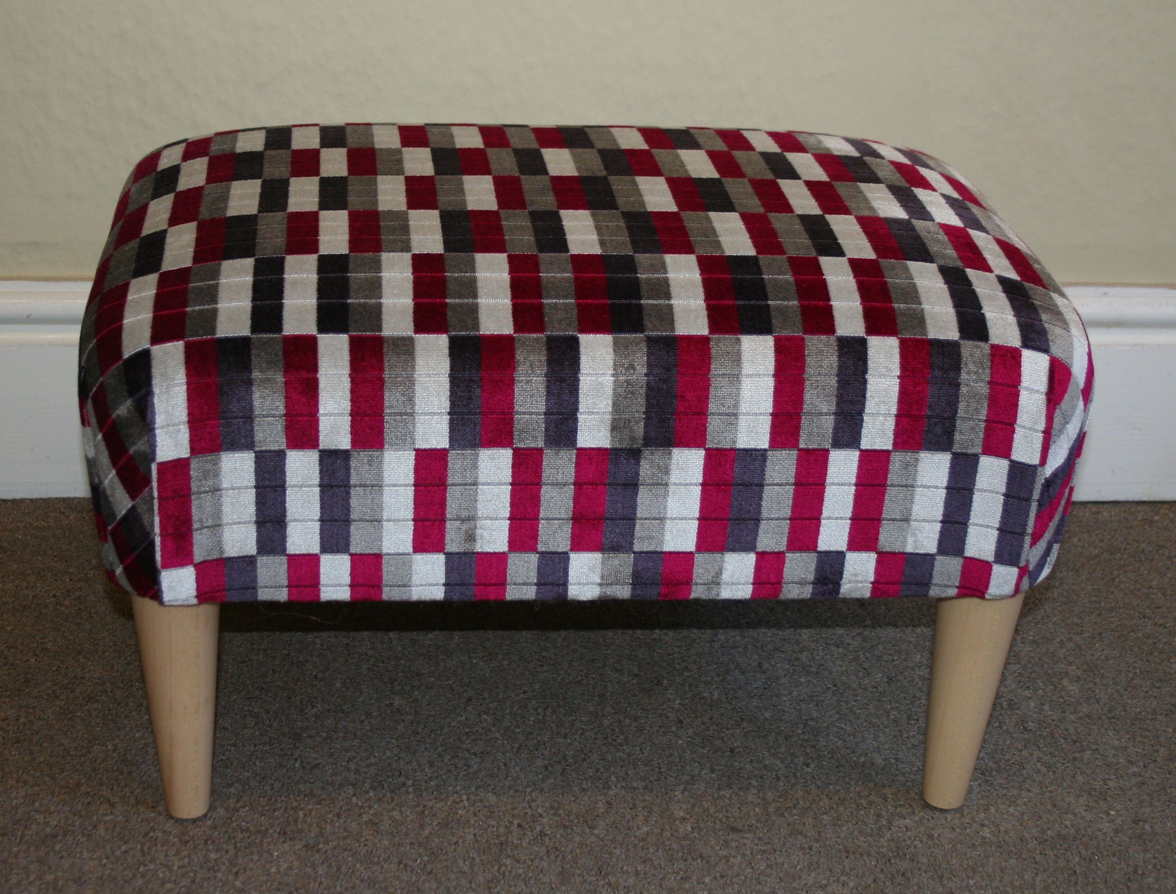 This small footstool has been upholstered in fabric from Kirkby Design Underground collection and is from the District line