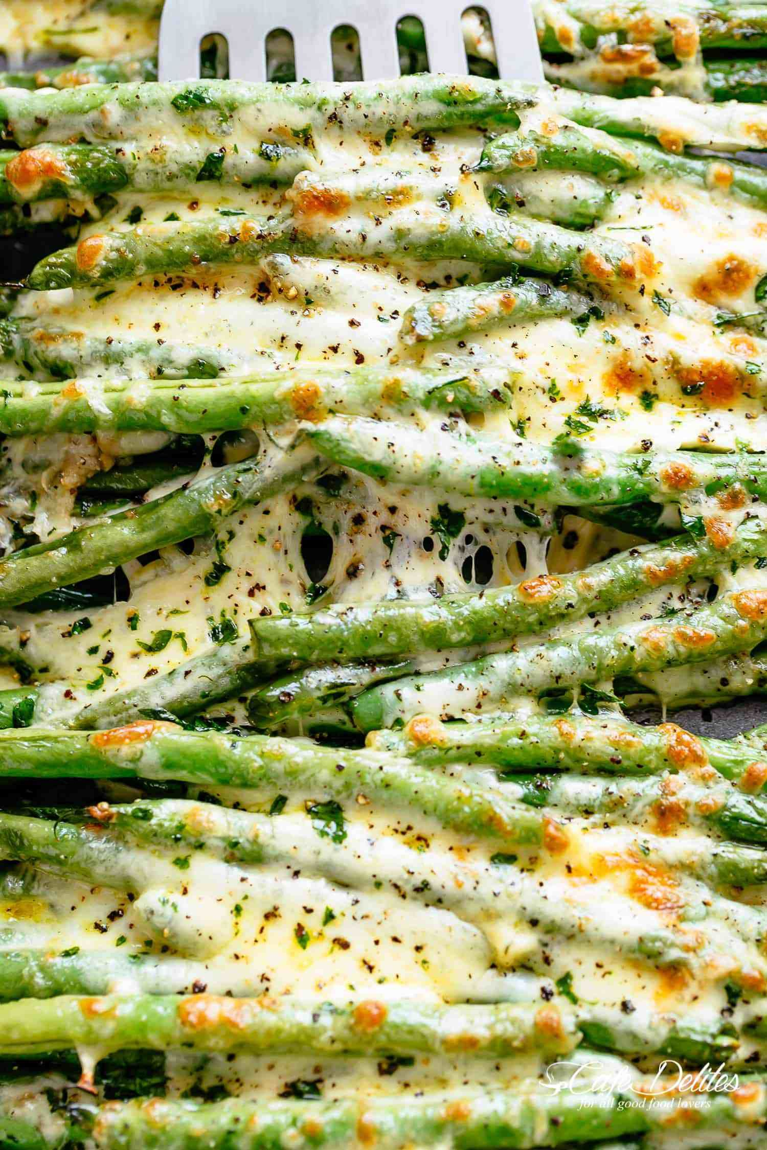 Roasted Green Beans are a deliciously easy side dish. Roasted in olive oil, garlic and parmesan, then baked with cheese until melted! #foodsides