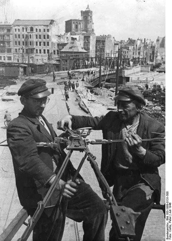 Berlin Juli 1946. An der Schließung der letzten großen Verkehrslücke im Straßenbahnnetz wird jetzt mit Hochdruck gearbeitet. Das Bild zeigt die Montagearbeiten an der Oberleitung der Strecke Spittelmarkt - Alexanderplatz an der Mühlendammbrücke.